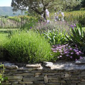 Une simple ganivelle en bois délimite avec légèreté et transparence le jardin en donnant le sentiment qu'il se prolonge sur la nature environnante.