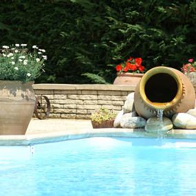 Quelques galets et pots traditionnels coiffés de fleurs colorées et judicieusement disposés suffisent à agrémenter harmonieusement le coin piscine.