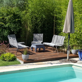 Grâce à cette petite terrasse en bois un recoin inutilisé du jardin est devenu un très agréable salon extérieur aux saveurs exotiques